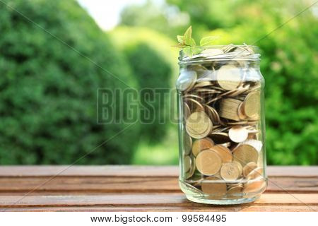 Coins in money jar on table outdoors