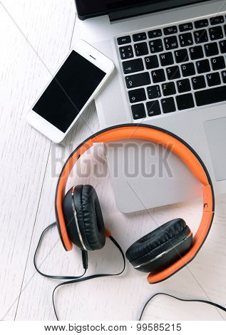 Headphones and other devices on worktop, closeup