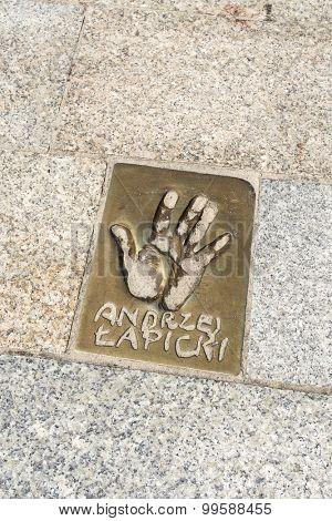 MIEDZYZDROJE, POLAND - AUGUST 16: Hand imprints in brass on a sidewalk of famed Polish movie star Andrzej Lapicki at