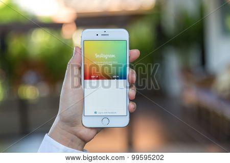 Loei, Thailand - August 12, 2015: Hand holding iPhone with mobile application for Instagram on the screen