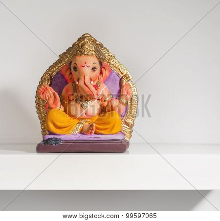 Small colorful Ganesha idol placed on a white shelf.
