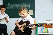 Cute pupils having music lesson in classroom at elementary school poster