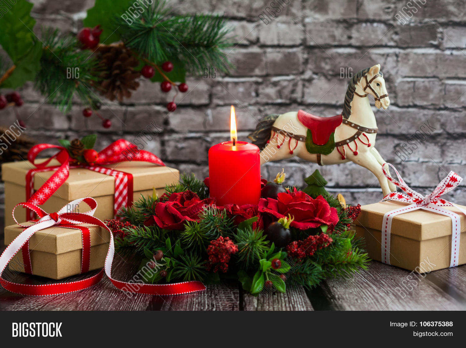 christmas decorations with red candlegift boxes and rocking horse on the old wooden table