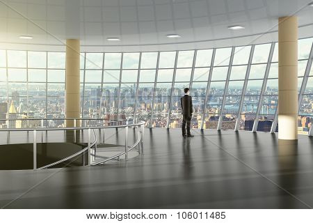 Businessman Standing In The Great Hall Of The Business Center, And Looks Towards The City