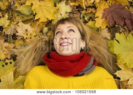 Young beautiful girl lying on autumn leaves and smiling