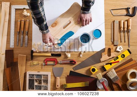 Decorator varnishing a wooden stool with a blue coating on a work table with DIY tools all around top view poster