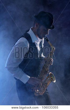 Elegant saxophonist plays jazz on dark background in blue smoke poster