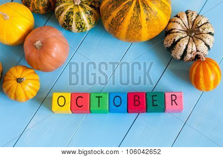 Autumn, many-coloured pumpkins frame, the word October on toy cubes, with light wooden background