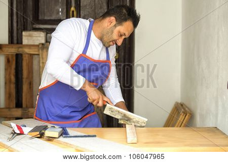 Carpenter Cutting With Handsaw In The Carpentry