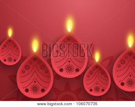 Floral decorated illuminated lit lamps on rangoli for Indian Festival of Lights, Happy Diwali celebration.