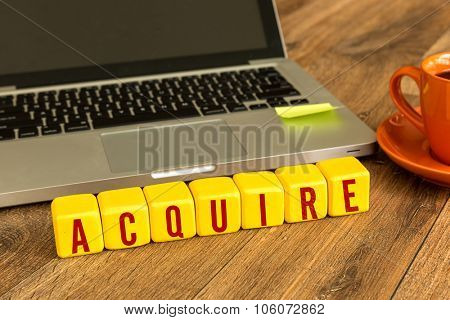 Acquire written on a wooden cube in front of a laptop