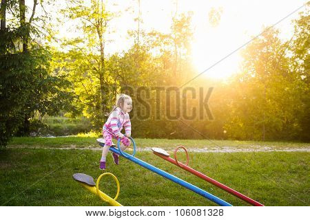 Happy Little Girl Playing, Going Up Ad Down On A Seesaw