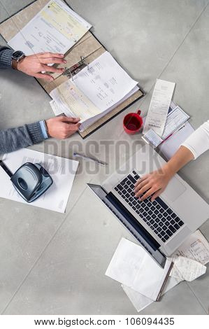 Hands, working with various kinds of paperwork, such as bills, receipts, invoices, doing accountancy with a laptop, seen from above on a concrete table surface