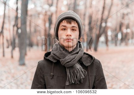 Serious teenage boy in a cap, scarf and jacket in the autumn sunny park. Toning in cool tones poster
