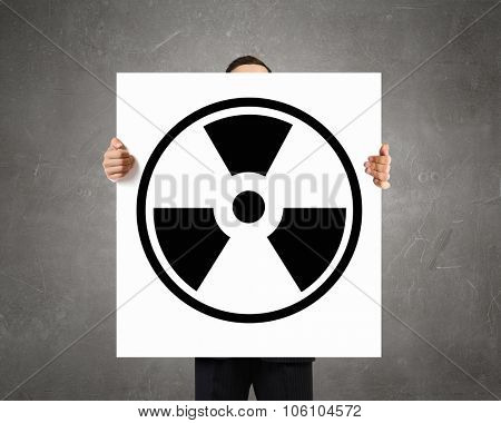 Businessman showing white banner with radioactive sign