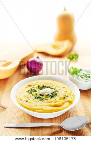Bowl of butternut squash soup with spoon and squashes