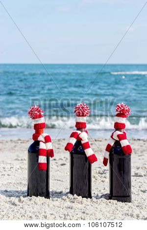 Christmas Gifts. Three Bottles Of Wine In Knitted Hats And Scarves On The Beach.