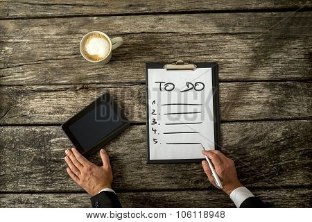 Top View Of Male Hand Writing A To Do List On A White Sheet Of Paper