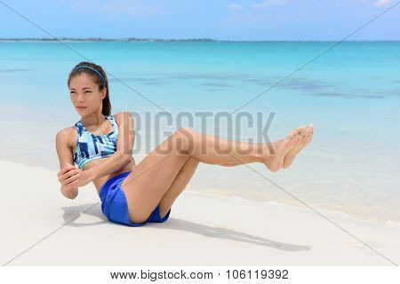 Abs workout - fitness woman working out on beach doing russian twists exercises with raised legs to tone body and train oblique muscles.
