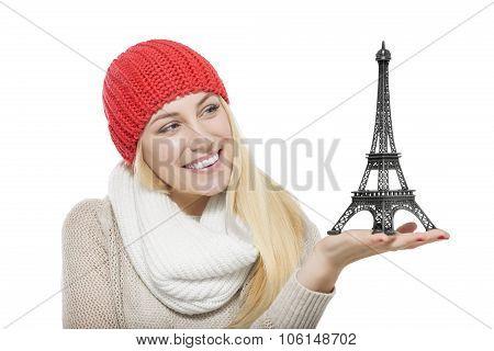 Beautiful blonde holding Eiffel Tower model.