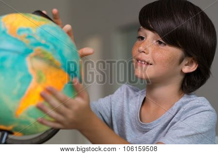 Closeup of little boy learning about the world using globe of earth. Male child studying globe at school. Cute boy looking at globe of earth.