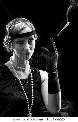 Woman in flapper dress in twenties style smoking a cigarette