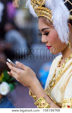 BANGKOK, THAILAND, February 17, 2015 : A Thai lady traditional dancer is checking her smartphone before the show celebrating the new Krung Kasem floating market in Bangkok, Thailand