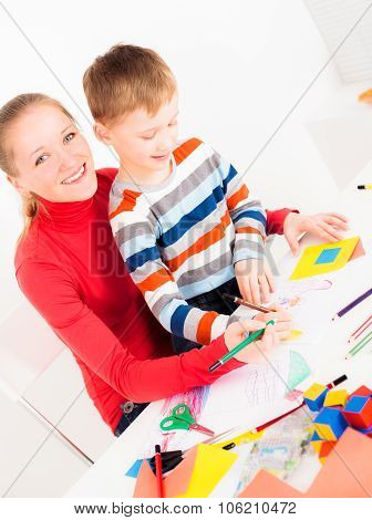 Smiling woman with her child drawing