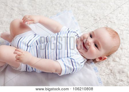 Smiling baby boy laying on bed