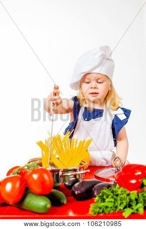 Little girl making pasta in pan