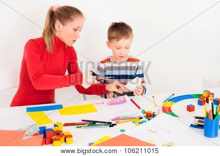 Mother teaching her son to cut the paper