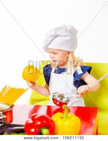 Cute little girl in cap cook with soup ladle in hand