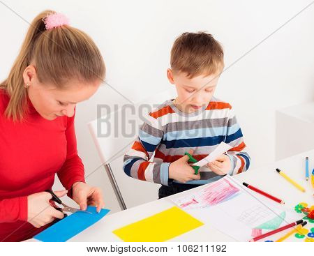 Mother and her son cuting colored paper
