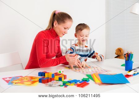 Son playing with his mom in board game