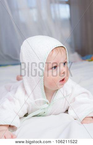 Cute boy in bathrobe laying on his belly