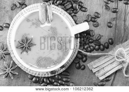 coffee on the cup with coffee beans and cinnamon sticks on wood background on balck and white selective focus poster