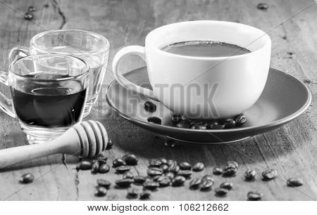 a cup of coffee with the honey on black and white selective focus poster