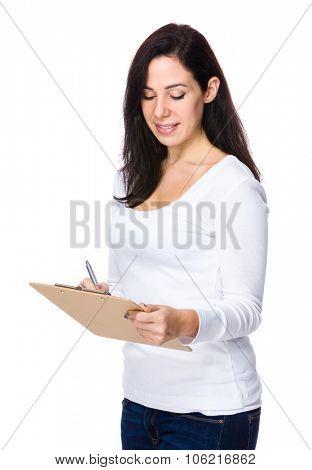 Brunette woman take note on clipboard