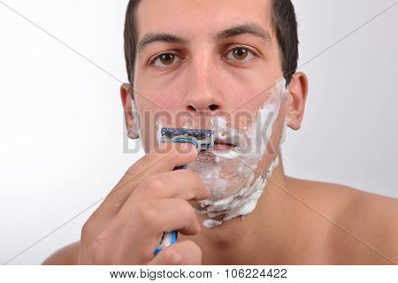 Handsome young man with lots of shaving cream on his face preparing to shave with razor poster