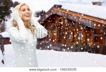 winter, fashion, vacation, christmas and people concept - smiling young woman in earmuffs and sweater over wooden country house and snowflakes background