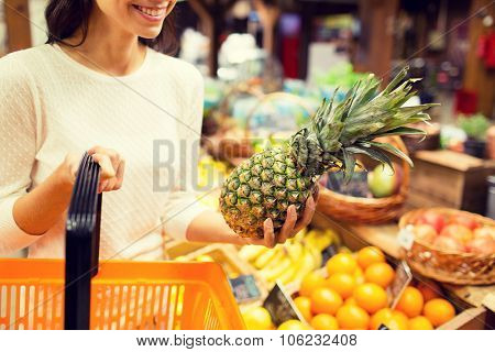 sale, shopping, consumerism and people concept - close up of young woman with food basket and pineapple in grocery market