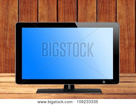 Modern Tv Screen With Blue Screen On Wooden Table