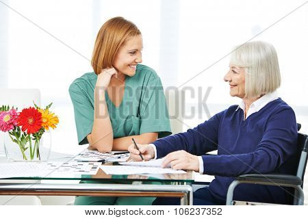 Smiling senior woman solving crossword puzzles next to nurse in nursing home