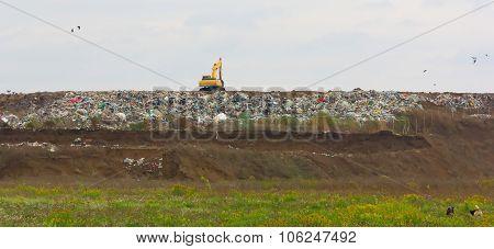 Excavator at the garbage dump