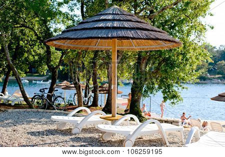 Sun Umbrellas And Lounges On The Costline In Porec, Croatia