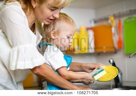 Mother teaches her little child son to wash-up