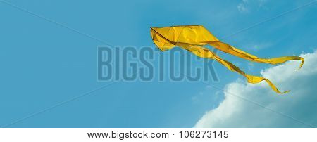 Yellow kite flying in the sky. Cloudy day. Blue background.