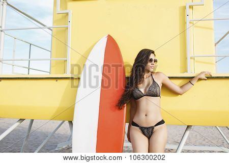 Portrait of a young stunning female resting after surfing in beautiful sunny summer day