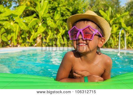 Happy boy in shaped sunglasses on green airbed
