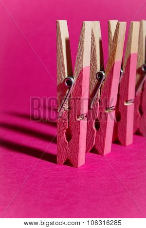 Row Of Pink Painted Wooden Pegs On Pink Background